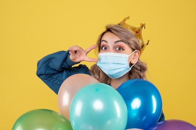 黄色の滅菌マスクで風船を保持している若い女性