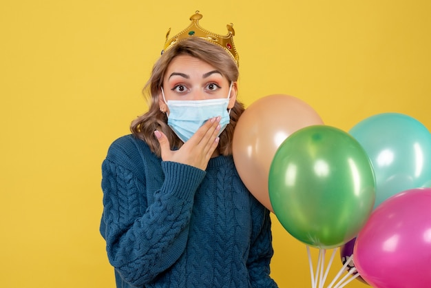 Young female holding balloons in sterile mask on yellow