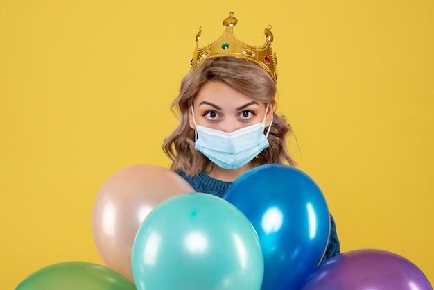 Giovane femmina che tiene palloncini in maschera sterile su giallo