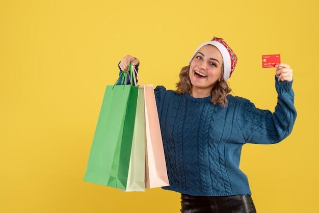 노란색에 쇼핑 후 은행 카드와 패키지를 들고 젊은 여성