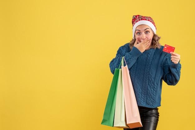 黄色で買い物をした後、銀行カードとパッケージを保持している若い女性