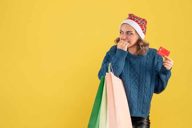 Young female holding bank card and packages after shopping on yellow