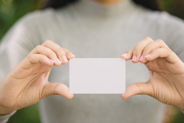 Young female holding blank credit card