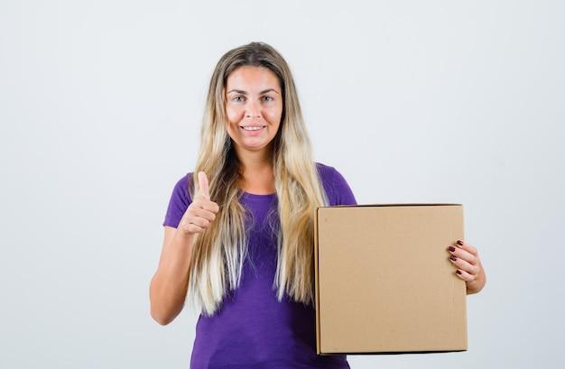 紫色のtシャツに親指を表示し、嬉しそうに見える、正面図の若い女性の保持ボックス。