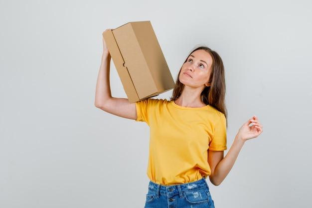 Молодая женщина держит картонную коробку и смотрит в футболку, вид спереди шорты.