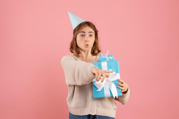 ピンクのクリスマスプレゼントを保持している若い女性