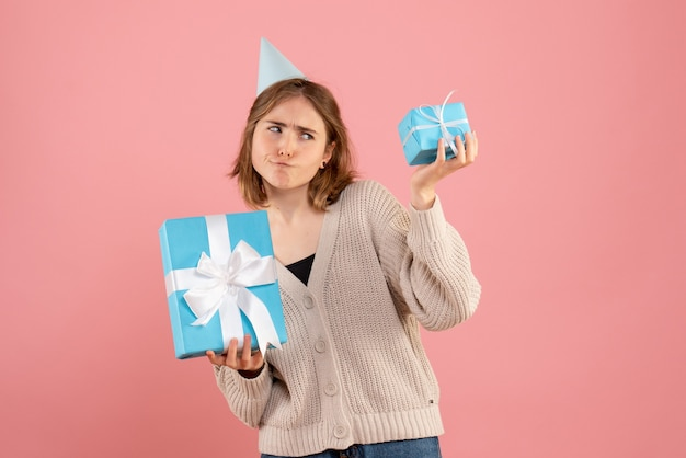 Young female holding christmas presents on pink