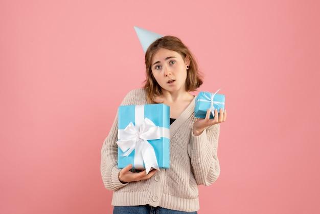 Giovane donna in possesso di regali di natale in rosa