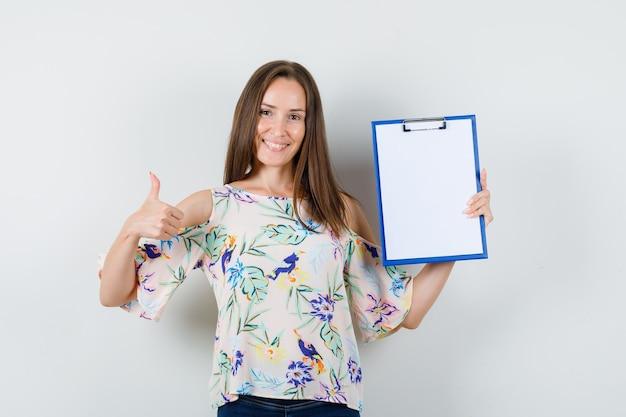 Молодая женщина держит буфер обмена с большим пальцем руки вверх в рубашке, джинсах и выглядит веселым. передний план.