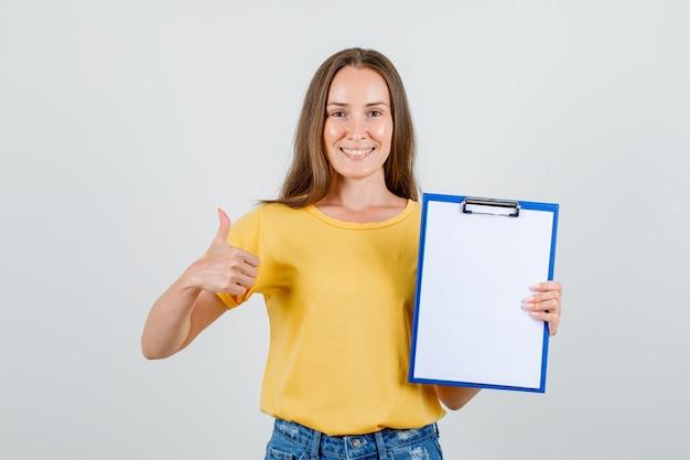 Tシャツ、ショートパンツ、幸せそうに見える親指でクリップボードを保持している若い女性。正面図。