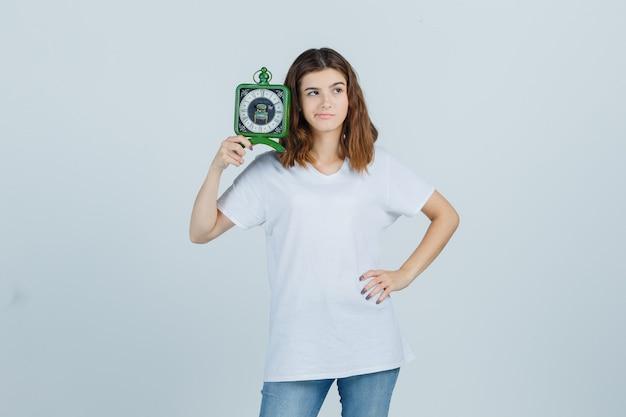白いtシャツ、ジーンズ、躊躇している、正面図で時計を保持している若い女性。