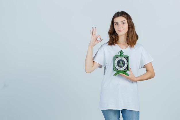 Giovane orologio femminile della tenuta, che mostra il gesto giusto in maglietta bianca, jeans e che sembra allegro, vista frontale.