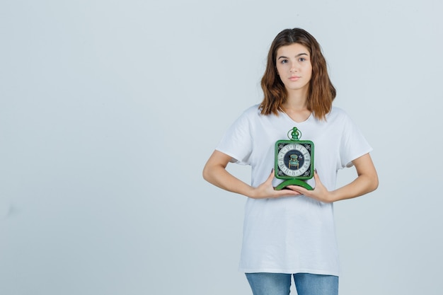 Young female holding clock in white t-shirt, jeans and looking sensible. front view.