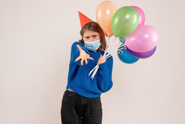 白のマスクでカラフルな風船を保持している若い女性