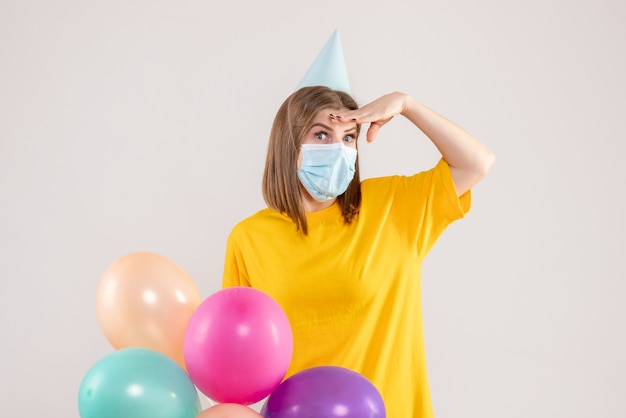 화이트 마스크에 다채로운 풍선을 들고 젊은 여성