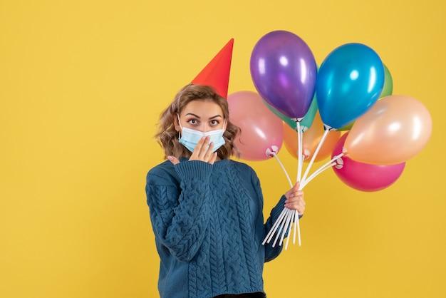 黄色のマスクでカラフルな風船を保持している若い女性