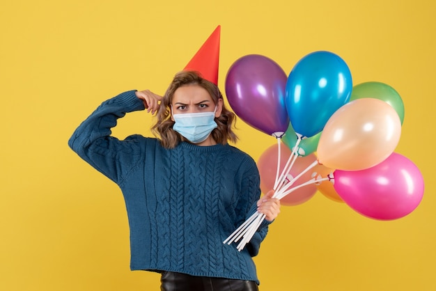 노란색 마스크에 다채로운 풍선을 들고 젊은 여성