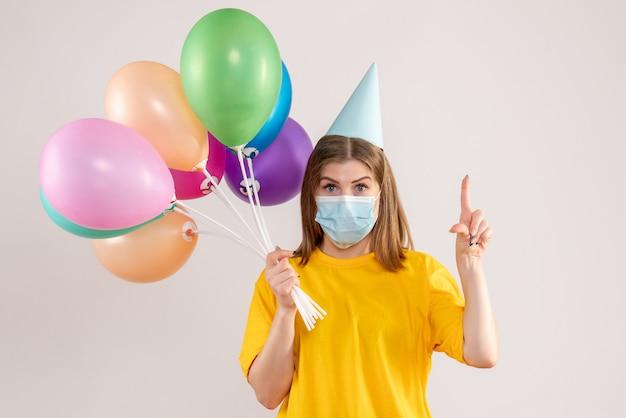 화이트에 살 균 마스크에 다채로운 풍선을 들고 젊은 여성