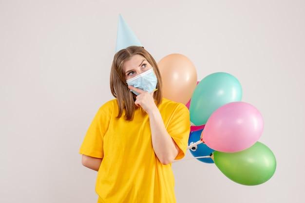 Giovane donna che tiene palloncini colorati in maschera pensando su bianco