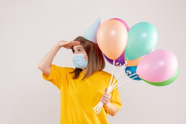 Giovane donna in possesso di palloncini colorati in maschera su bianco