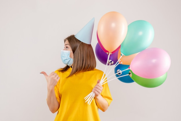 Young female holding colorful balloons in mask on white