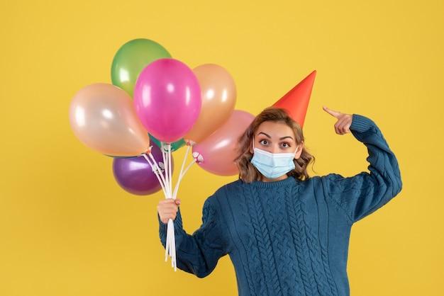 Giovane donna in possesso di palloncini colorati in maschera sul giallo