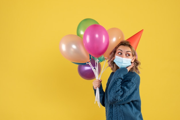 Young female holding colorful balloons in mask on yellow