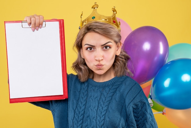 Young female holding colorful balloons and note on yellow