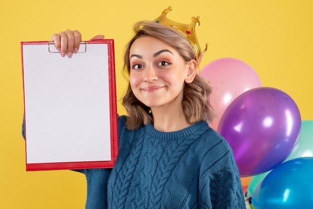 Giovane donna in possesso di palloncini colorati e nota su giallo