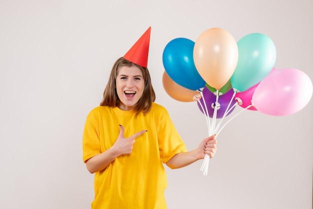화이트에 다채로운 풍선을 들고 젊은 여성