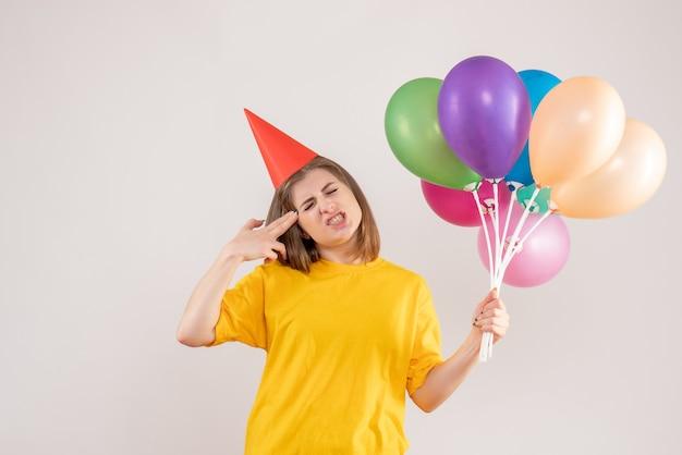 白でカラフルな風船を保持している若い女性