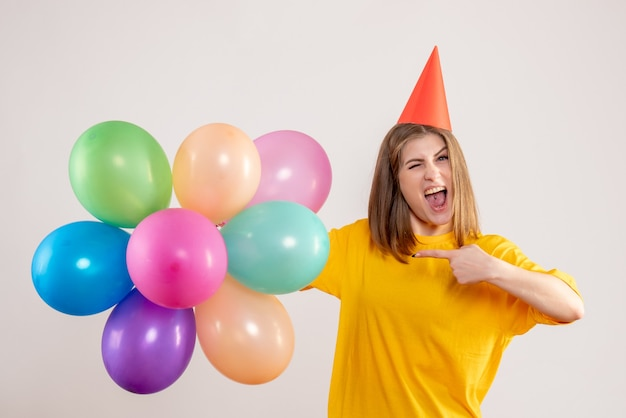 Молодая женщина держит разноцветные воздушные шары на белом