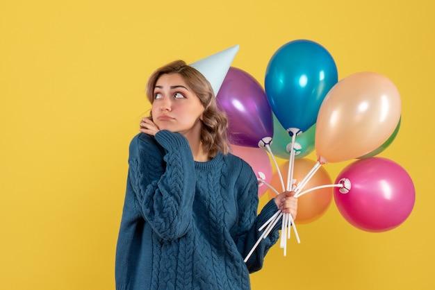 黄色のカラフルな風船を保持している若い女性