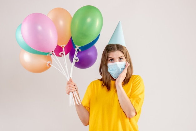 Young female holding colorful balloons in sterile mask on white