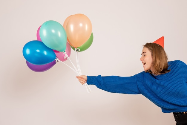Young female holding colorful balloons on white