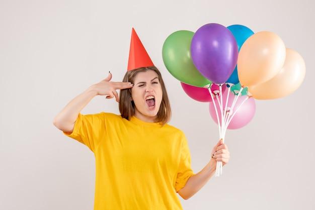 Giovane femmina che tiene palloncini colorati su bianco