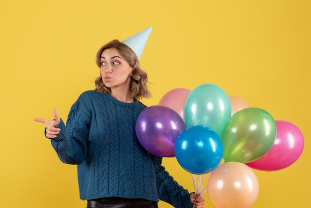 Young female holding colorful balloons on yellow