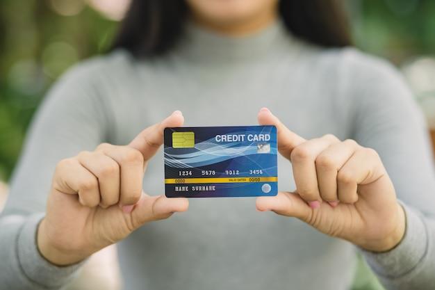 Молодая женщина, держащая кредитную карту