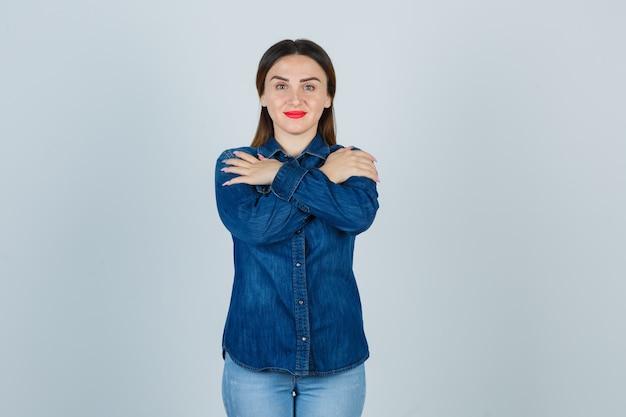デニムシャツとジーンズで肩に交差した手を保持し、陽気に見える若い女性
