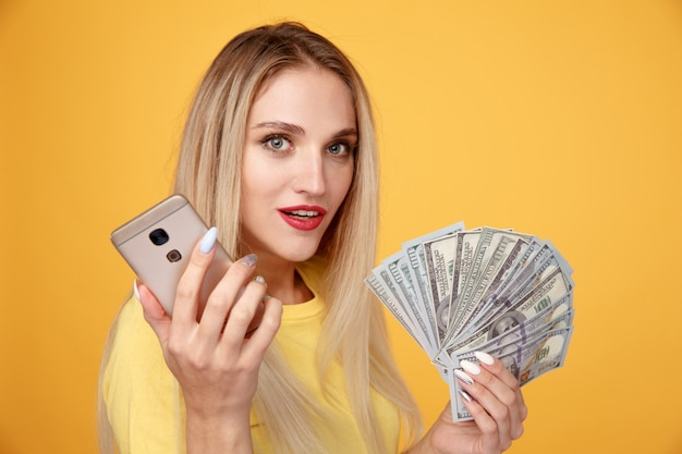 Young female holding dollar cash isolated.