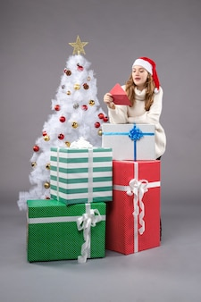 Young female holding envelop on gray floor new year holiday christmas