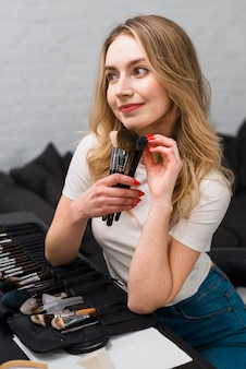 Young female holding few makeup brushes at table
