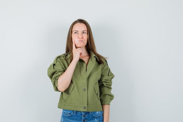 Giovane donna che tiene il dito sulla guancia soffiata in giacca, pantaloncini e guardando esitante, vista frontale.
