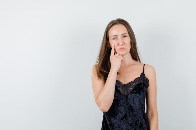 Giovane donna che tiene il dito sulla guancia in canottiera nera e sembra pietosa