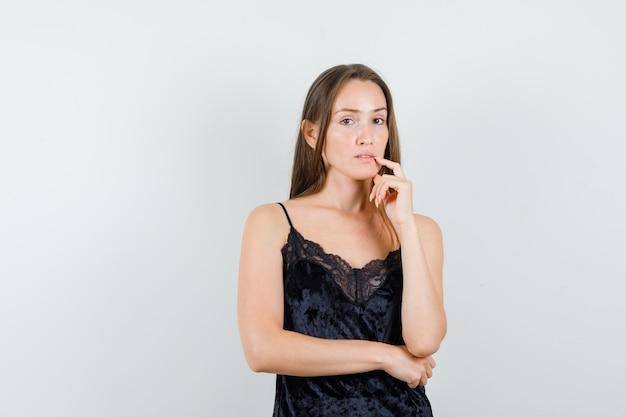 Giovane donna che tiene il dito vicino alla bocca in canottiera nera e sembra ragionevole