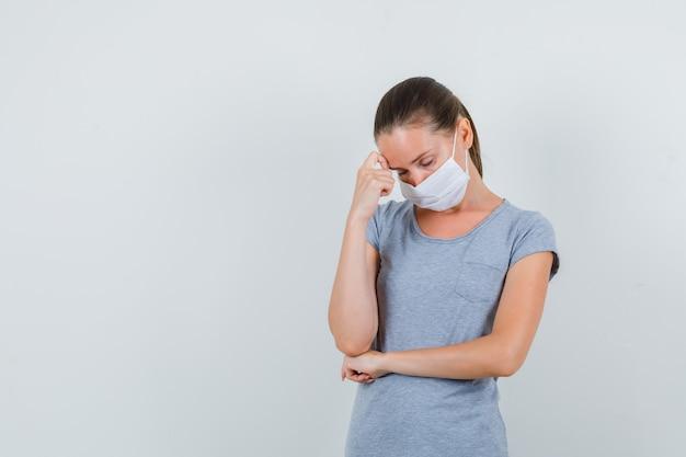 Молодая женщина держит палец на лбу в серой футболке, маске и выглядит измотанным. передний план.
