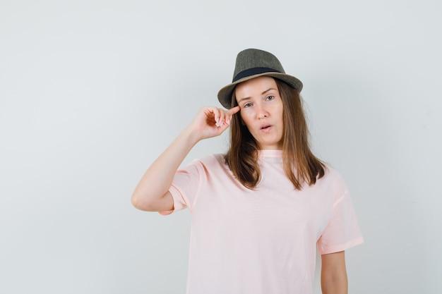 ピンクのtシャツ、帽子で寺院に指を持って、賢明に見える若い女性。正面図。