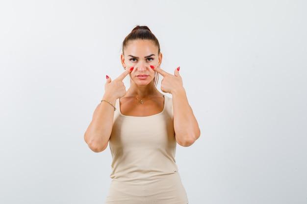 Giovane donna che tiene le dita sulle guance in canottiera beige e guardando fiducioso, vista frontale.