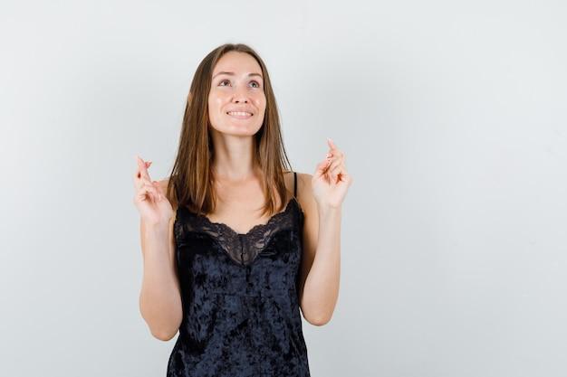 Giovane donna che tiene le dita incrociate in canottiera nera e sembra sognante.