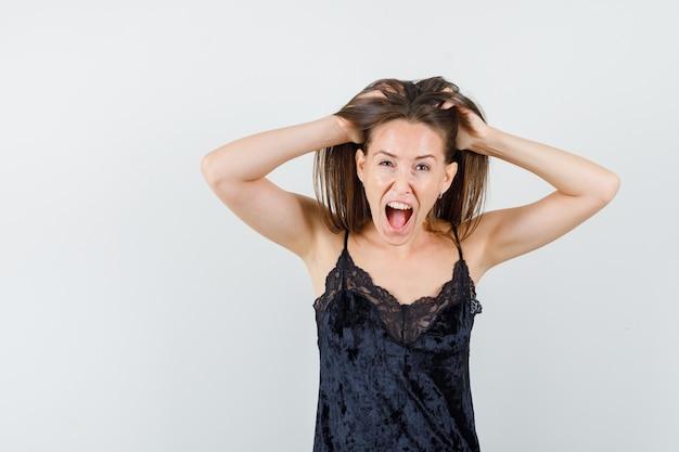 Giovane donna che tiene le dita nei capelli mentre grida in canottiera nera e sembra pazza.